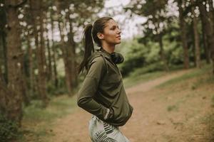 ung vacker kvinnlig löpare som lyssnar på musik och tar en paus efter att ha joggat i en skog foto