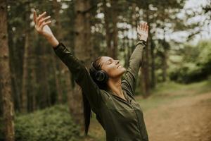 ung kvinna med hörlurar som armar armarna i skogen för att hon tycker om att träna ute foto