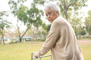 asiatisk senior eller äldre gammal damkvinnas patientvandring med rullator i park med kopieringsutrymme foto
