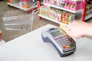 hand svepande kreditkort på betalningsterminal i butik foto