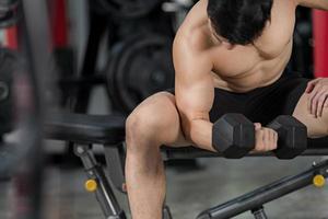 sportig man utbildning med hantel i gymmet foto