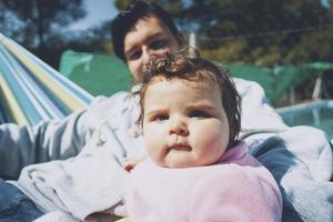 liten bebis njuter av en solig dag på semester med pappa foto