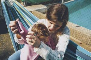 ung kvinna som bryr sig sitt barn sitter på en hängmatta foto