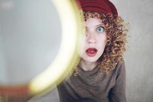 närbild porträtt av en vacker och ung rolig kvinna med blå ögon och lockigt blont hår undersöker med ett förstoringsglas och hon är förvånad foto