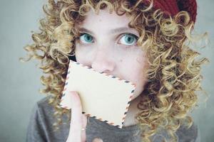 närbild porträtt av en vacker och ung rolig kvinna med blå ögon och lockigt blont hår med ett brev hon är misstänksam mot meddelandet foto