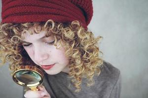 närbild porträtt av en vacker och ung rolig kvinna med blå ögon och lockigt blont hår undersöker med ett förstoringsglas foto