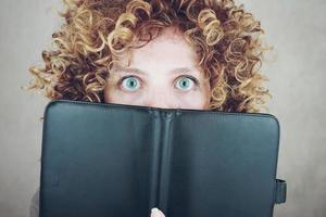 närbild porträtt av en vacker och ung rolig kvinna med blå ögon och lockigt blont hår hon är bakom en agenda eller e-bok och hon är förvånad foto