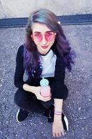 glad vacker tonåring med rosa solglasögon dricker och njuter av en rosa dryck som sitter på stadsmarken foto
