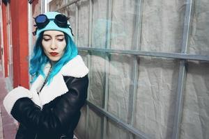 porträtt av en punk eller gotisk ung kvinna med blått färgat hår och bär svarta steampunk-glasögon och blå ullmössa i en stadsgata utomhus foto
