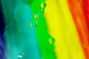 ett vackert och färgstarkt makro av oljebubblor på vatten med en gul, röd, grön, orange och blå randstruktur som bakgrundsmönster foto