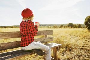 en ung kvinna bakifrån i röd rutig skjorta med ulllock och halsduk som tar en kopp te eller kaffe medan hon solar sittande i en träbänk i ett gult fält med bakgrundsbelysning från höstsolen foto