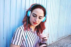 vacker rödhårig kvinna lyssnar på musik foto