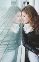 ung vacker kvinna reflekteras i ett stort fönster foto