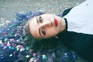vacker ung kvinna omgiven av konfetti foto