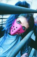 ung punk kvinna som bär en rosa mask foto