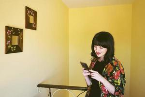 vacker brunett kvinna i ett gult rum i hennes hem foto