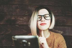 blond kvinna som använder sin mobiltelefon foto