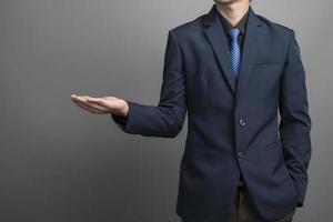 närbild av affärsmannen i blå kostym som håller något på grå bakgrund foto