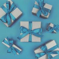 presentaskar förpackade i hantverkspapper med blå band och rosetter. festlig monokrom platt låg. foto