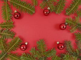 jul ram med granar grenar och grannlåt på en röd bakgrund. festlig lägenhet låg med kopia utrymme inuti. stock foto. foto