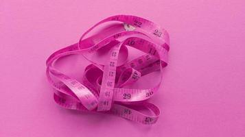 rosa centimeter på rosa bakgrund. enkel platt låg med pastellstruktur. fitness koncept. stock foto. foto