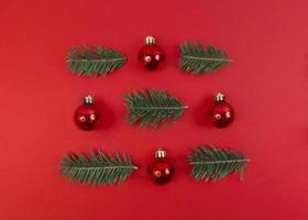 julsymmetri sammansättning från leksakstruntsaker och granar på en röd bakgrund. enkel festlig platt låg. foto