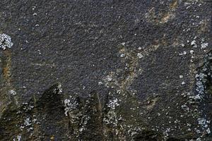 svart sten konsistens med sprickor och chips, bakgrundsbild foto
