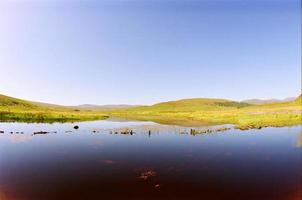 gröna ängar och blå sjö foto