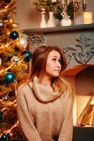 söt flicka bland juldekorationer ser upp. foto