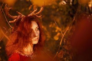 kvinna i lång röd klänning med hjorthorn i höstskog. foto