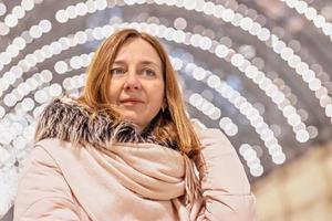 en vacker ung kvinna står i ett köpcentrum med en bokeh med många glödlampor i bakgrunden. foto