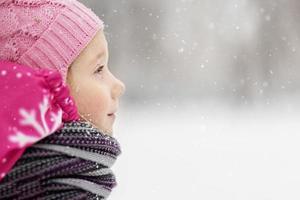 porträtt av en liten flicka i rosa närbild. ett barn njuter av snöfallet. jullov foto