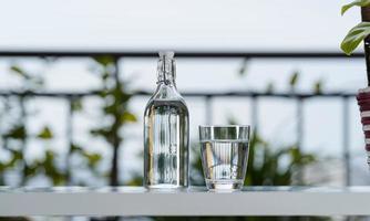 drick vattenflaska med glas på bordet hemma i trädgården foto