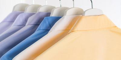 herrklänningskjortor, kläder på galgar på vit bakgrund foto