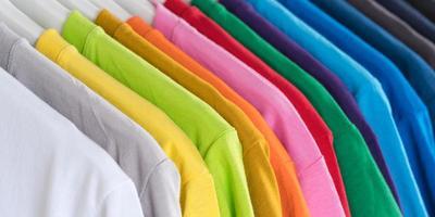 närbild av t-shirts, kläder på galgar på vit bakgrund foto