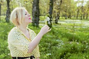 kvinna som blåser en maskros foto