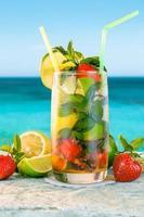 mojito cocktail. vit romcocktail med färska ingredienser. kall isdryck på suddig strandbakgrund. foto