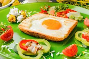 ägg i rostat bröd bakat i form av en blomma med färska grönsaker foto