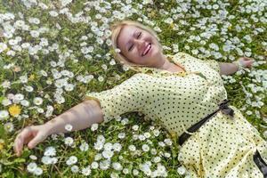 blond flicka tycker om att ligga på en äng full av blommor foto