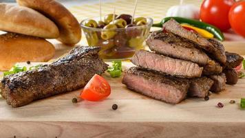 grillat nötkött på träplatta med grönsaker och oliver i bakgrunden. foto