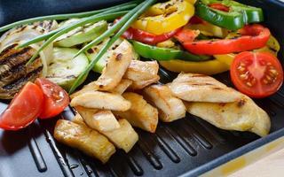grillat kycklingkött på grill med grönsaker i bakgrunden. foto