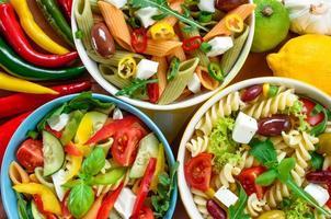 tre pastasallad med tomat, rucola, gurka, paprika, varm paprika, svarta och gröna oliver och ostfeta. foto