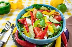 pastasallad med tomat, rucola, gurka, paprika, het paprika, svarta och gröna oliver och ostfeta. toppvy. foto