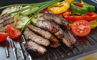grillat nötkött på grill med grillade grönsaker i bakgrunden. foto
