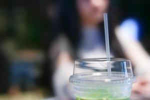 iced matcha grönt te latte på bordet med kvinnor som arbetar i butik foto