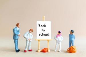 lärare och elever nära duk på staffli med ordet tillbaka till skolan foto