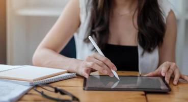 kvinna som rymmer den digitala minnestavlan och pennan på hennes kontorsskrivbord foto