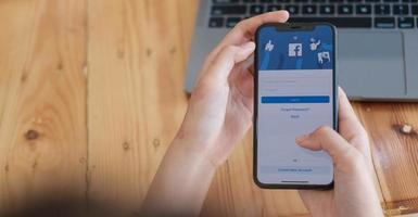 Chiang Mai, Thailand 18 aug 2020 - kvinna som håller en iPhone x med social internet-tjänst Facebook på skärmen. foto