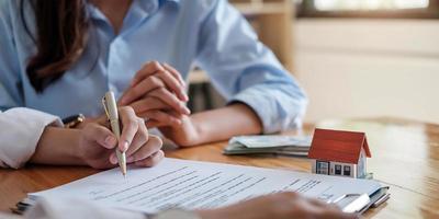 erfaren fastighetsmäklare som visar husmodell för kunden och redo att skriva ett kontrakt foto