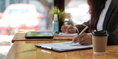 affärskvinna som använder miniräknare för matematikfinansiering på träbord i kontor och affärsarbetsbakgrund, skatt, redovisning, statistik och analytisk forskningskoncept foto